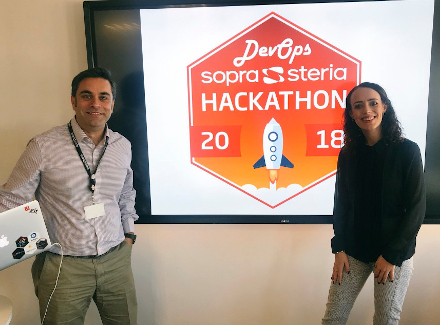 Photo of Sopra Steria employees Shehzad Nagi and Caitlin Toner in front of the Sopra Steria DevOps 2018 Hackathon logo